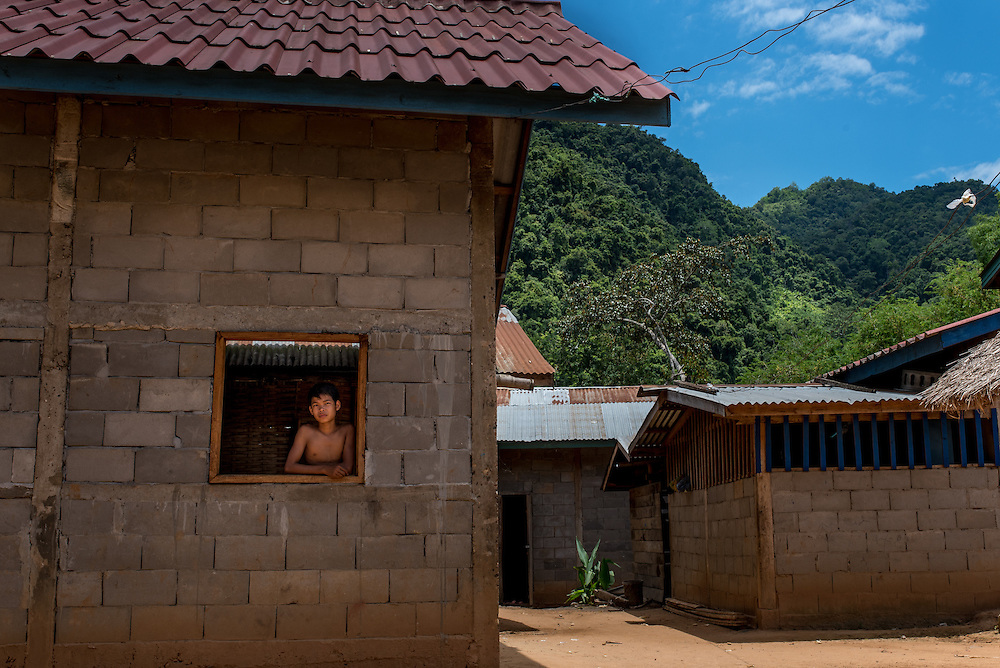 A boy stands in the window of his home in the village of Khoc Kham.