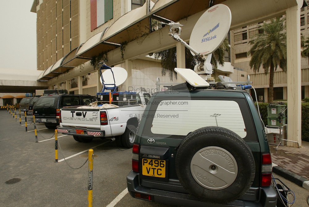 Television crews outfit their SUV's with satellite transmitters and gear for covering the Iraq war at the Sheraton Hotel in Kuwait City.