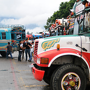 Chicken buses lined up behind the Mercado Municipal (town market) in Antigua, Guatemala. From this extensive central bus interchange the routes radiate out across Guatemala. Often brightly painted, the chicken buses are retrofitted American school buses and provide a cheap mode of transport throughout the country.