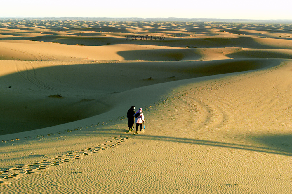 View at sunrise toward the south across the rolling Sahara, toward a flat horizon. In the foreground, footprints of a couple walking along in close conversation.