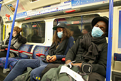 © Licensed to London News Pictures. 17/03/2020. London, UK. Commuters wearing face masks travel on a Piccadilly Line train. London Transport will reduce weekday services during the coronavirus crisis to a weekend level of service. Photo credit: Dinendra Haria/LNP