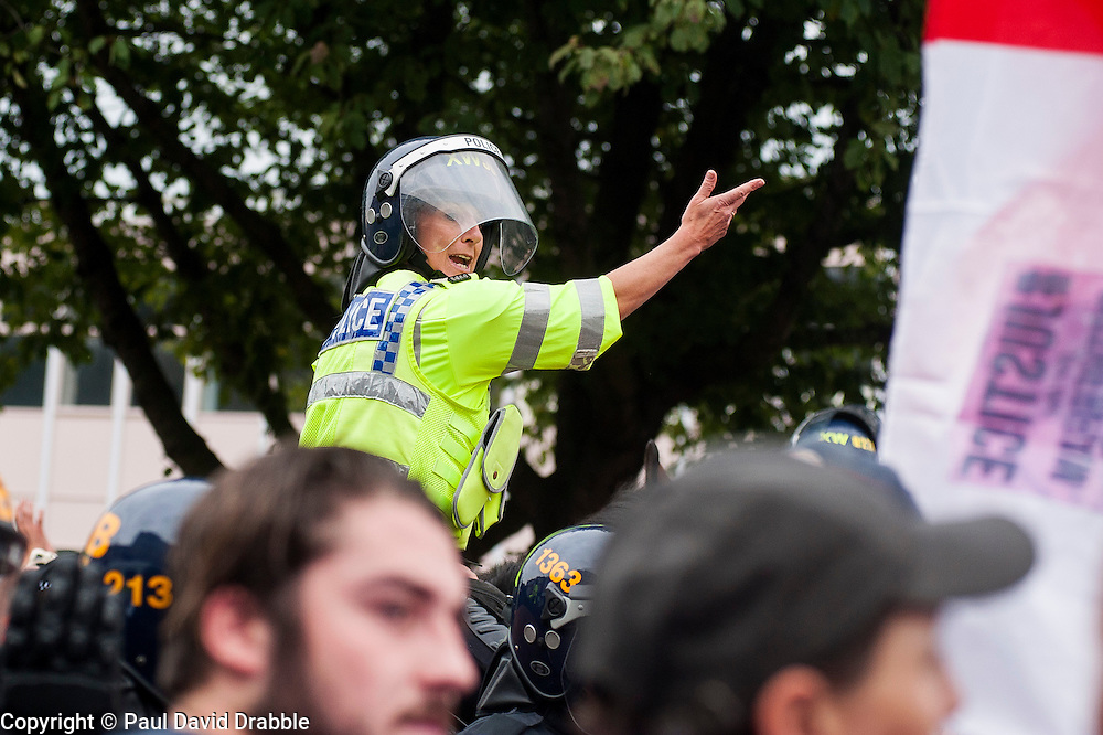 "Rotherham England<br /> 13 September 2014 <br /> A mounted police officer directs EDL members and supporters away from a potential trouble spot during the EDLs ""Justice for the Rotherham 1400"" march described by an EDL Facebook Page as ""a protest against the Pakistani Muslim grooming gangs"" on Saturday Afternoon <br /> <br /> <br /> Image © Paul David Drabble <br /> www.pauldaviddrabble.co.uk"
