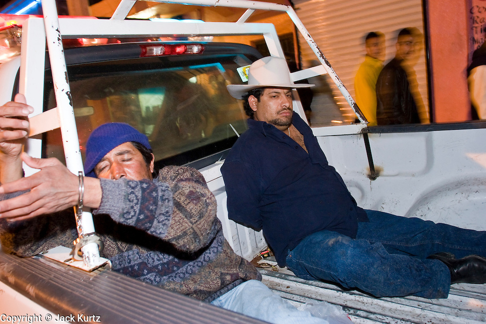 "05 FEBRUARY 2005 - NOGALES, SONORA, MEXICO: Men who were arrested by Nogales police sit in the back of a police truck during an anti-gang sweep. Members of ""Grupo Operativos"" a special operations unit of the Nogales, Sonora, Mexico, police department, on patrol in Nogales, Saturday night, Feb. 5. The Operativos specialize in anti-gang enforcement and drug interdiction missions. In recent months they have stepped up patrol activity in Nogales communities near the border. In January 2005, the US Department of State has issued a travel advisory advising US citizens to avoid travel along the US Mexican border because of increased violence, including the kidnapping of US citizens, in border communities. Most of the violence has been linked to the drug cartels, who are increasingly powerful in Mexico. The Operativos also patrol the districts of Nogales frequented by US tourists in an effort to prevent crime directed against US citizens.   PHOTO BY JACK KURTZ"