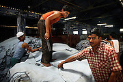 Workers inside the warehouse of a large tannery in Jajmau Industrial Area, Kanpur, Uttar Pradesh, are counting, stockpiling and measuring pieces of dry leather while cutting out some impurities and scraps. They will then proceed with smoothing, colouring and finishing.