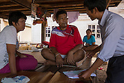 Mr Bunsri Mamak, 50, (red) receives a follow-up visit from Gumphol Wongsuvan of Sapphasit Prasong hospital at his house after spending 13 days in ICU in Ubon's Provincial Hospital after contracting Melioidosis from his fields. He is diabetic and after the symptoms of Melioidosis were wrongly diagnosed at 3 different health clinics and local hospitals he was finally rushed to Sapphasit Prasong hospital that has a Melioidosis clinic and specialised laboratory where Mr Gumphol works.<br /> <br /> Melioidosis, though hardly heard of, is Thailand's third largest killer after AIDS and TB. Experts estimate that Melioidosis, caused by a shape-shifting bacteria that lives in water and soil, has 165,000 new cases world-wide a year and that more than half result in death. That means Melioidosis kills roughly the same number as measles or dengue across the globe. <br /> <br /> The bacteria is highly endemic in Northeast Thailand where around 2000 cases are reported per year and mostly from rice farmers who have regular contact with the soil. If not treated and the patients have other complications such a diabetes the mortality rate can be as high as 90% within 5 days.<br /> <br /> If a patient is treated, every case involves a minimum of 2 weeks in hospital followed by 20 weeks of antibiotic treatment and annual followups for the rest of their lives.<br /> <br /> Melioidosis, placed in the same microorganism grouping as anthrax by the US government, is a deadly neglected tropical disease that very few have even heard of.
