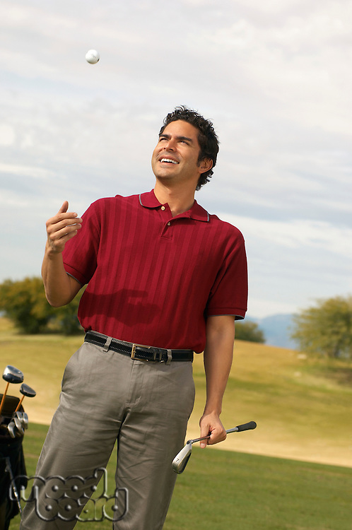 Golfer Holding Putter Tossing Golf Ball in Air
