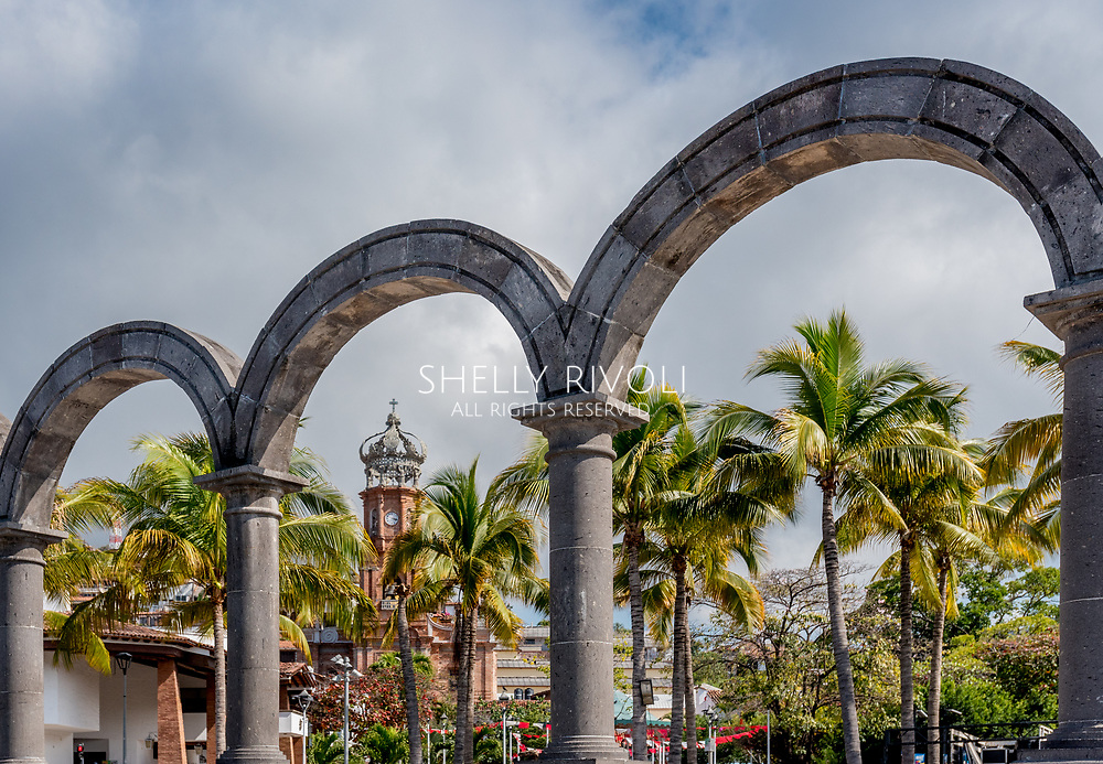 View of Puerto Vallarta through the arches or los arcos on the Malecon showing Old Town or Old Vallarta and Our Lady of Guadalupe Church tower.