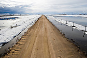 Spring snow melt on the Camas Prairie in Southwest Idaho contrast against a recently flooded dirt road