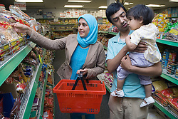 Young family shopping for food in supermarket