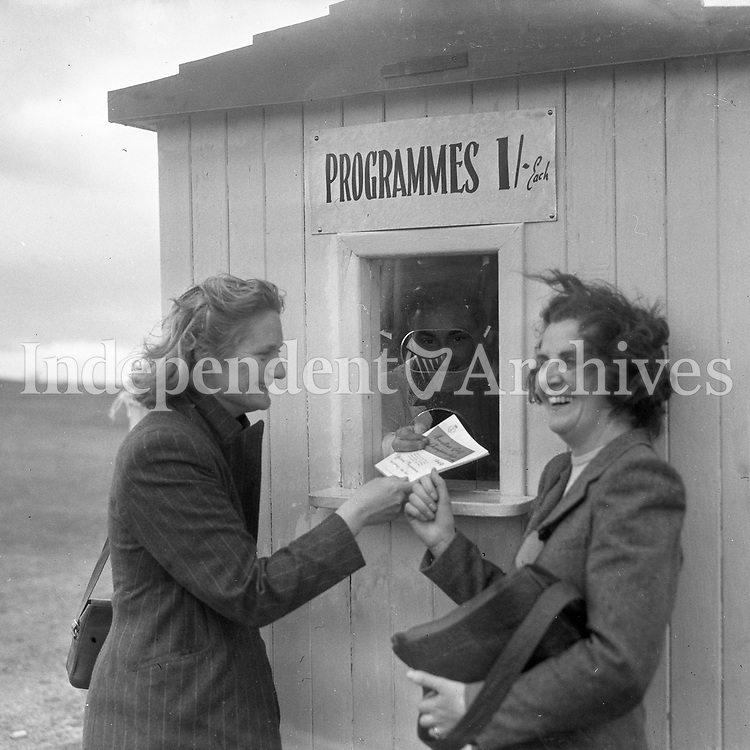 Two ladies buying programmes from a man in a booth. Possibly golf or horse-racing.<br />
