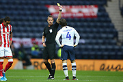 Referee John Brooks shows Preston North End midfielder Ben Pearson (4) the yellow card during the EFL Sky Bet Championship match between Preston North End and Stoke City at Deepdale, Preston, England on 21 August 2019.