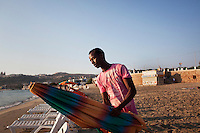 """Mellieha, Malta - 19 August, 2012:  Hassan Mahamed Dalmar, 21, places an umbrella on the beach of Mellieha Bay, Malta, on 19 August, 2012. Hassan left Somalia in 2007 and went to Djibouti, Eritrea, Sudan, Libya and arrived in Malta in 2009 after paying a smuggler $900 to board a boat with 160 immigrants. After 7 days, the boat had finished its gas, food and water. They were saved by a Finnish ship that brought them to Malta. A finnish worker who helped Hassan told him: """"You are born again now. Pray the Lord and start a new life"""". Upon his arrival in Malta he was put in a detention center for 12 months. His application for refugee status was rejected. He made it to Belgium in August 2011 and was deported back to Malta in January 2012. Upon his return he was imprisoned for 4 months for traveling illegally. He was released on May 28, 2012. Since then he has been working, sleeping outdoors and living in the beach of Mellieha Bay, where he sets up umbrellas and sunbeds from 6:30am to 7:30pm.<br /> <br /> Some immigrants work, live, sleep and eat for the entire summer season in the Maltese beaches. Their work consists of waking up at 6:30am and unpile and place sunbeds, cushions and umbrellas at the beach before tourists arrive. Upon their arrival at the beach, tourists are guided by the migrants to the spot they choose. Umbrellas and sunbeds cost 5 euros each. The toursts pay the migrants, whom brings the money to the owner. Each migrant is paid 25 euros a day. By 9am, there are about 90 umbrellas and 180 sunbeds ready for the tourists.<br /> <br /> Gianni Cipriano for The New York Times"""