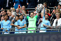 Manchester City goalkeeper Ederson (centre) and Bernardo Silva celebrate with the FA Cup trophy at the end of the match