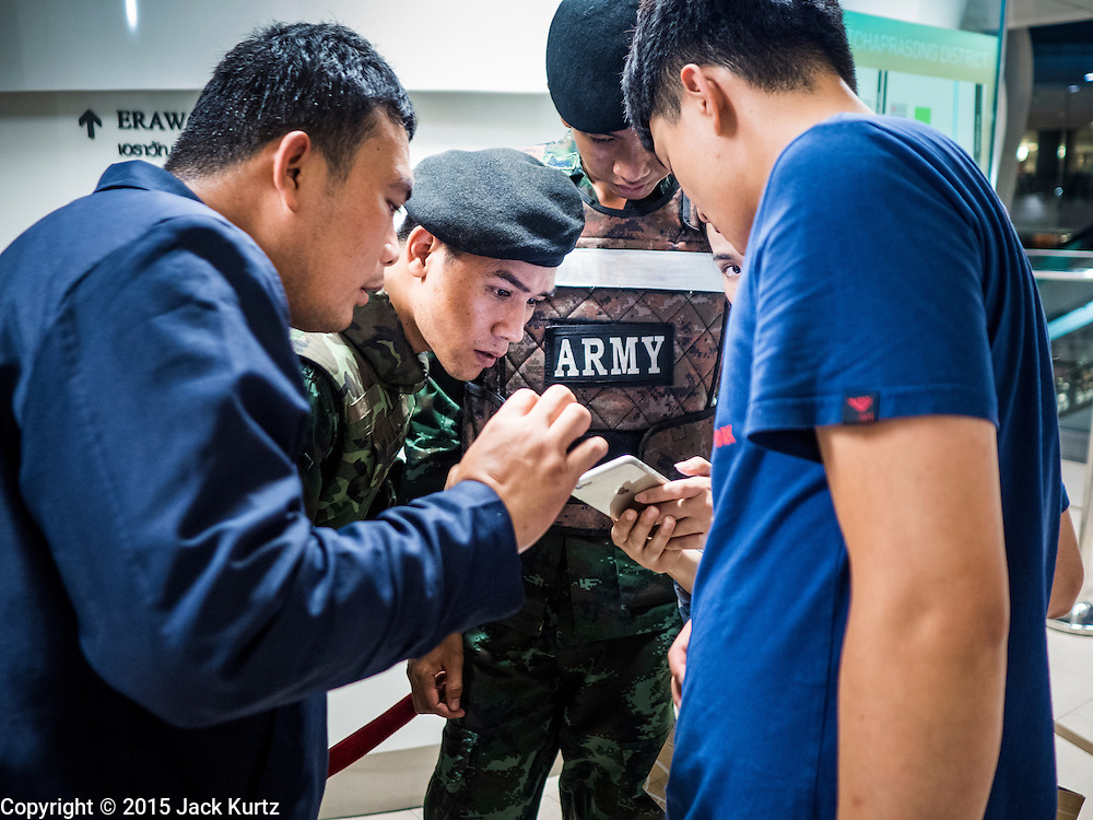 17 AUGUST 2015 - BANGKOK, THAILAND: Thai soldiers help Asian tourists find their hotel on a map in Chit Lom BTS Station after and explosion at Erawan Shrine shut down central Bangkok. An explosion at Erawan Shrine, a popular tourist attraction and important religious shrine, in the heart of the Bangkok shopping district killed at least 19 people and injured more than 120 others, mostly foreign tourists, during the Monday evening rush hour. Twelve of the dead were killed at the scene. Thai police said an Improvised Explosive Device (IED) was detonated at 18.55. Police said the bomb was made of more than six pounds of TNT stuffed in a pipe and wrapped with white cloth. Its destructive radius was estimated at 100 meters. The Bangkok government announced that public schools would be closed Tuesday as a precaution.        PHOTO BY JACK KURTZ
