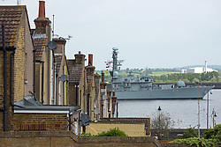 © Licensed to London News Pictures. 16/05/2016. HMS Kent passes an old terrace in Gravesend, Kent. The Type-23 frigate HMS Kent has left London after a short stay to head towards commemorative events to mark the centenary of the Battle of Jutland. She leaves London for Rosyth, a major port and key ship building area of the First World War, where she will take part in events organized by the Scottish Government at South Queensferry. She will then sail for Scapa Flow where she will provide a gun salute. Credit : Rob Powell/LNP