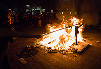 NOVEMBER 9, 2016 - OAKLAND, CA: An Anti-Trump protester displays an effigy of Donald Trump as protesters start a fire on Broadway and 17th Street, in Oakland, California on November 9, 2016. (Photo by Philip Pacheco)