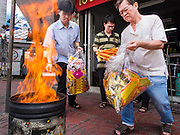 "10 AUGUST 2014 - BANGKOK, THAILAND: Men pour ""joss paper"" into a burn barrel on the first day of Ghost Month in Bangkok. Joss paper also known as ghost money, are sheets of paper and/or paper-crafts made into burnt offerings. The seventh month of the Chinese Lunar calendar is called ""Ghost Month"" during which ghosts and spirits, including those of the deceased ancestors, come out from the lower realm. It is common for Chinese people to make merit during the month by burning ""hell money"" and presenting food to the ghosts.    PHOTO BY JACK KURTZ"