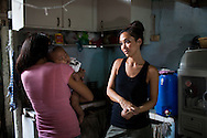 UK celebrity Myleene Klass (in black) meets underprivileged mother Irma Asoro, 29, as she holds her 4-month-old baby, Rashed James, who she has been feeding formula since he was 2 days old, in her rented home in an urban slum in Paranaque, Metro Manila, The Philippines on 19 January 2013. She thinks that formula is better for her baby even though the cost of formula and bottled water costs her more than double her rent, and she has to borrow from family and friends to pay for it. Photo by Suzanne Lee for Save the Children UK