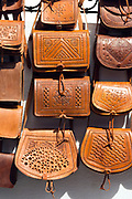 CHEFCHAOUEN, MOROCCO - 27th APRIL 2016 - Leather shopping and hand bags hang for sale in the souks of the Chefchaouen Medina - the blue city - Rif Mountains, Northern Morocco.