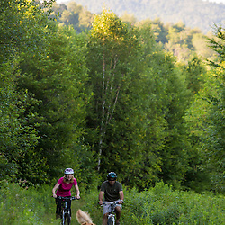 A couple rides their mountain bikes on the edge of a forest in Duxbury, Vermont.