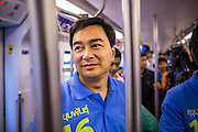 16 FEBRUARY 2013 - BANGKOK, THAILAND:   ABHISIT VEJJAJIVA, former Prime Minister of Thailand, rides the BTS Skytrain while he campaigns for his party colleague Sukhumbhand Paribatra ahead of Bangkok's governor election. Bangkok residents go to the polls on March 3 to elect a new governor. Sukhumbhand Paribatra, the current governor, is running on the Democrat's ticket and is getting help from national politicians like Abhisit Vejjajiva, the former Thai Prime Minister. One of Sukhumbhand's campaign pledges is to improve Bangkok's mass transit and transportation system. Abhisist road the BTS Skytrain to campaign for Sukhumbhand.    PHOTO BY JACK KURTZ