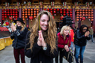 Annie Dingwall, front, of Texas, with her friend Nicki, left, and Nancy Spencer, 2nd right, pray at the Hsi Lai Temple in Hacienda Heights, California on Friday, January 31, 2014, on the Chinese Lunar New Year. Worshippers visited the temple for the New Year of the Horse and to pray for happiness and prosperity.(Photo by Ringo Chiu/PHOTOFORMULA.com)