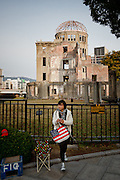 Hiroshima, November 27 2011 - An Asian tourist with a american bag in front of the atomic bomb dome.