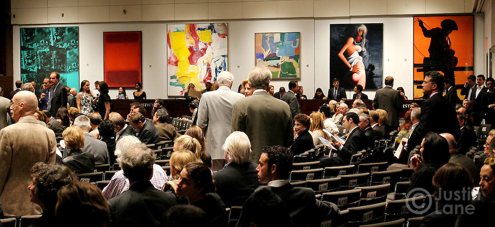 Auction patrons look for seats before the start of auction where Andy Warhol's 'Green Car Crash (Green Burning Car I)' (seen at far  left) was sold for $71,720,000 (USD) at Christie's auction house in New York, New York on 16 May 2007. The sale amount was a record for a Warhol. Also pictured, from 2nd left, is Mark Rothko's 'Untitled', Williem de Kooning's ''Untitled I', Richard Diebenkorn's 'Berkeley #5', Lisa Yuskavage' 'Night' and Richard Price's 'Untitled (Cowboy)'.