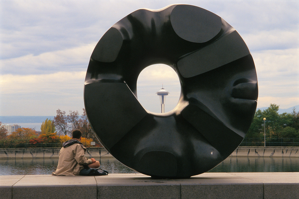 The Space Needle seen through the doughnut-shaped sculpture Black Sun by artist Isamu Noguchi in Volunteer Park, Seattle, Washington.