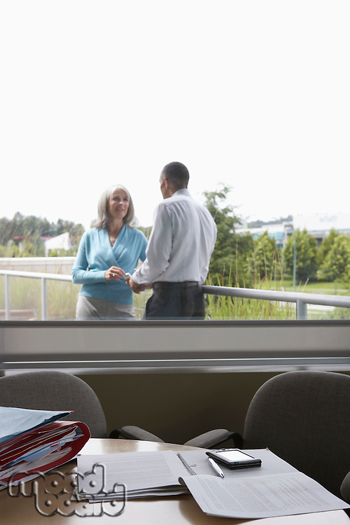 Business couple talking on terrace view through window