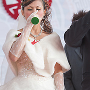 Newlywed bride drinks champagne at traditional Taiwanese wedding in Namasiya Township, Kaoshiung County, Taiwan