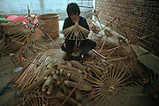 A worker at a Thai umbrella factory in Chiangmai hand crafts bamboo and silk parasols.