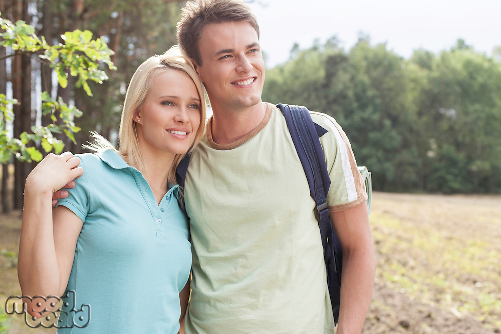 Thoughtful young couple smiling while hiking in forest