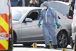 © Licensed to London News Pictures. 13/04/2019. London, UK. A forensics officer is seen working next to a car with a smashed window in Holland Park after shots were fired by police near the Ukranian embassy. Photo credit: Peter Macdiarmid/LNP