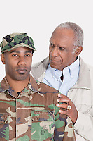 Portrait of an African American US Marine Corps soldier with father over gray background