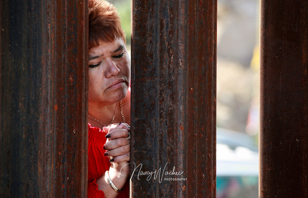 A woman in Mexico peers through the slats of the border fence as a group of U.S. bishops celebrate Mass in Nogales, Ariz., April 1. About a dozen bishops took part in a two-day visit to the border with Mexico calling attention to the plight of migrants and appealing for changes in U.S. immigration policy. (CNS photo/Nancy Wiechec) (April 1, 2014) See BORDER-MASS April 1, 2014.