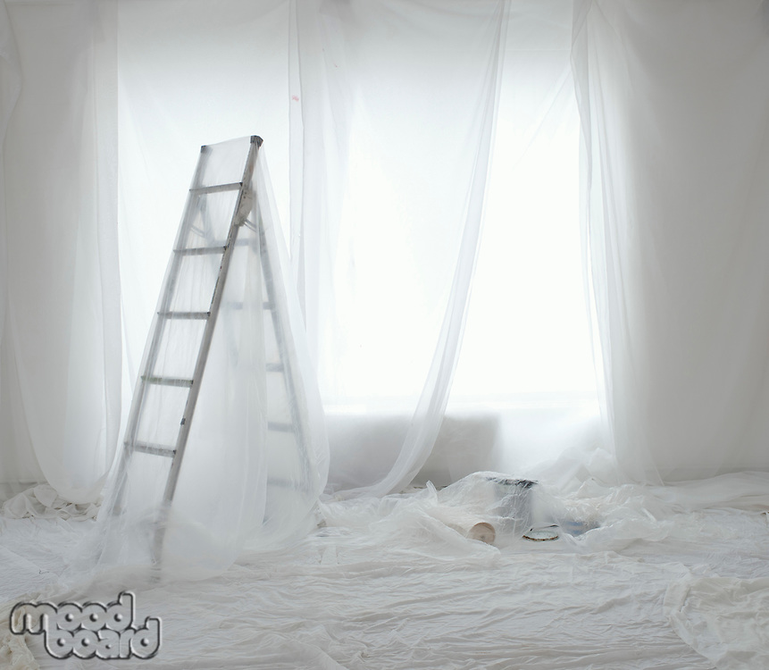 Empty room covered in transparent dust sheets prepared for painting and decorating