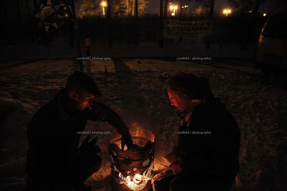 Two man lights a camp fire in front of Gorleben nuclear sites. Anti nuclear activists protest while a sylvester party (2009-2010) against the future plans to implement a final dump of nuclear waste in Gorleben. The protesters welcomed the new year by fireing fireworks towards the sites tower. Police just observed the scenery.