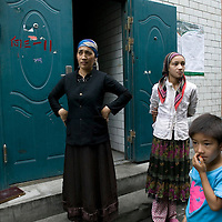URUMQI, JULY-15 : Uighur migrants stand in Urumqi's Xiangyang Po district, a poor quarter of the city dominated by Uighurs, Turkic-speaking Muslims who have often had an uneasy relationship with China's Han majority. Uighurs are the largest ethnic group in Xinjiang, but in Urumqi, Han make up more than 70 percent of the 2.3 million residents.<br /> Many Han Chinese were killed in Xiangyang Po during the protests in early July 2009.