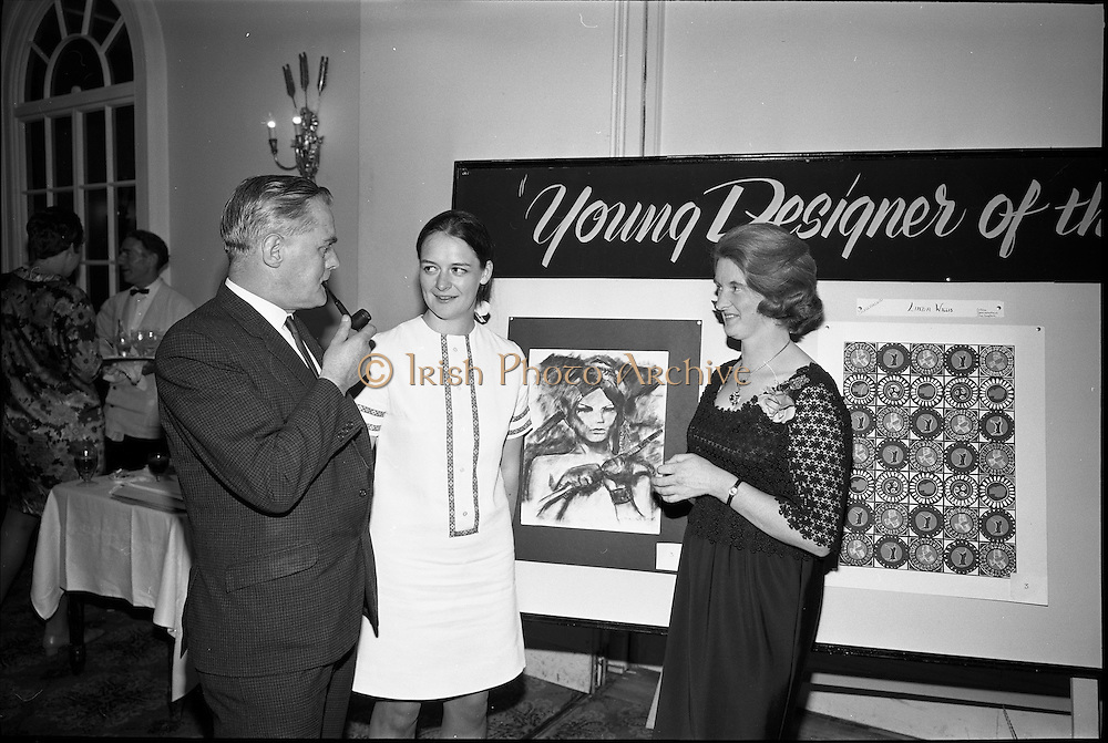"""28/06/1967<br /> 06/28/1967<br /> 28 June 1967<br /> Presentation of prizes at Navan Carpets """"Young Designer of the Year"""" reception in the Royal Hibernian Hotel, Dublin. Image shows Ms Linda Willis (20) a College of Art student from Dun Laoghaire, who was named Ireland's """"Young Designer of the Year"""". Linda, who was born in Venice, received her prize with the other award winners at the reception. Left -right are:  Mr. Allan Mallinson, Managing Director, Navan Carpets Ltd.; Miss Willis and Miss V. Sheridan, Navan Carpets Ltd. standing in front of Linda's design."""