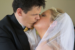 Visually impaired bride and groom kissing at wedding.