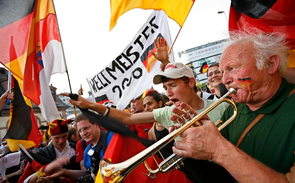 Frankfurt | Deutschland 24.06.2006: Fu&szlig;ballfans schauen das Achtelfinalspiel zwischen den Deutschland und Schweden in der Main Arena in Frankfurt und feiern anschlie&szlig;end in der Frankfurter Innenstadt den Sieg der deutschen Mannschaft.<br /> <br /> hier:  Ein &auml;lterer Mann mit Trompete begleitet die Fanges&auml;nge und wird von begeisterten Fans auf den Schultern getragen, w&auml;hrend ein Plakat Deutschland schon zum Weltmeister 2006 erkl&auml;rt.<br /> <br /> Sascha Rheker<br /> 20060624<br /> <br /> [Inhaltsveraendernde Manipulation des Fotos nur nach ausdruecklicher Genehmigung des Fotografen. Vereinbarungen ueber Abtretung von Persoenlichkeitsrechten/Model Release der abgebildeten Person/Personen liegt/liegen nicht vor.]