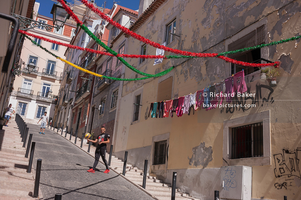 Young men play an impromptu kick-about with a football on a steep street on 13th July 2016, in Bairro Alto district, Lisbon, Portugal. Thousands of impassioned Portuguese sports fans have very recently cheered their national football team days after the Euro 2016 final victory against France. (Photo by Richard Baker / In Pictures via Getty Images)