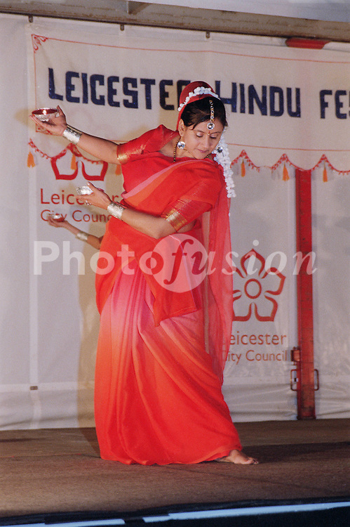 Woman wearing traditional sari dancing on stage to celebrate Diwali; festival of light,