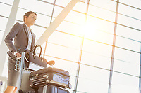 Young attractive businesswoman pushing baggage cart for check in at airport