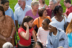 Large multiracial group of people talking and laughing with each other,
