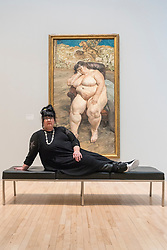 "© Licensed to London News Pictures. 26/02/2018. LONDON, UK. Sue Tilley sits with a painting of herself by Lucian Freud ""Sleeping by the Lion Carpet"", 1996. ""Preview of ""All Too Human"", an exhibition at Tate Britain which explores how artists in Britain have stretched the possibilities of paint in order to capture life around them.  The exhibition runs 28 February to 27 August 2018 and includes rarely seen works by Lucian Freud and Francis Bacon.  Photo credit: Stephen Chung/LNP"