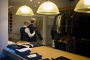 A gentleman client has a fitting for a new made-to-measure suit, seen through a City taylor's window.