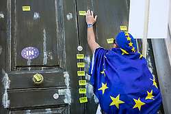 © Licensed to London News Pictures. 20/10/2018. London, UK. A protester sticks an anti-Brexit sticker to the door of the Cabinet Office as protesters join the People's Vote March in central London to call on government to give the public a vote on the final Brexit deal. Photo credit: Rob Pinney/LNP