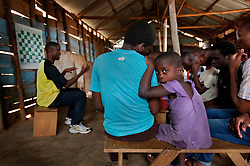 Phiona Mutesi, center, a 14-year-old chess prodigy, at the Agape Church inside Katwe, the largest slum in Kampala, Uganda, Dec. 8, 2010. Mutesi lives in the slums of Uganda and is just now learning to read. But her instincts have made her a player to watch in international chess. Mutesi, a naturally talented chess player is coached by Robert Katende of Sports Outreach Ministry. The chess club meets at the Agape Church.